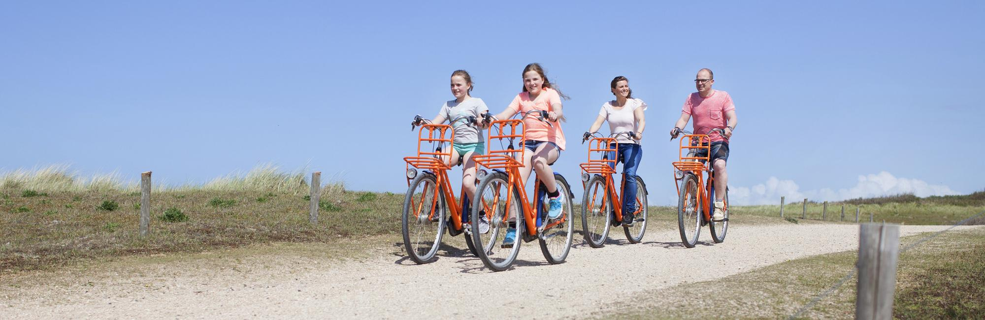 Family cycling in Holland by the beach